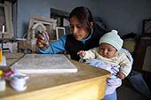 Mother carving tombstones while taking care of her baby. Potosí, Bolivia.